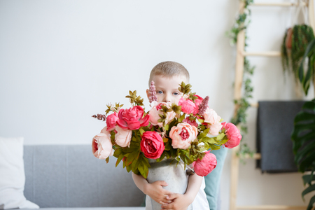 Image of boy with bouquet of pink peonies