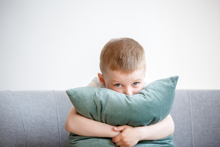 Photo of boy with pillow sitting on couch Imagens