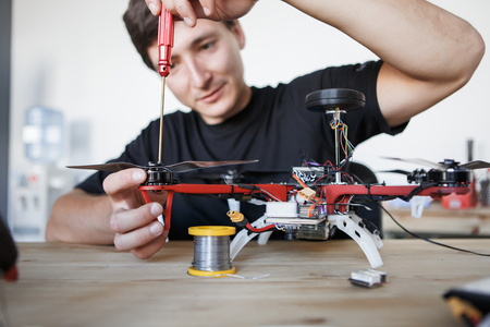 Picture of man with screwdriver fixing square copter at table Stock Photo