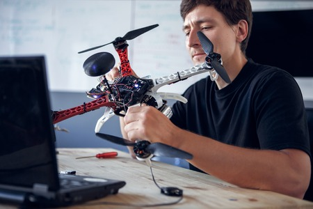 Photo of man fixing square copter at table