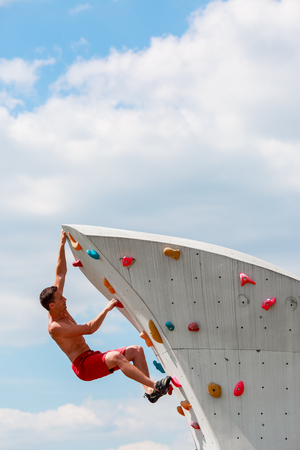Photo of trained sports guy in red shorts practicing on wall for rock climbing against blue sky with clouds Stock Photo
