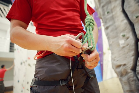 Close-up photo of male climber with safety rope in hands at sports hall indoors
