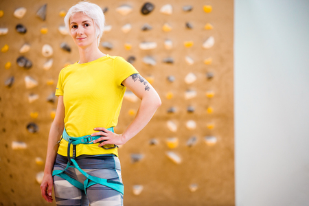 Photo of young woman in sports clothes and safety belts on climbing wall in sports hall