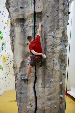Photo from back of man climbing up boulder in gym Banque d'images