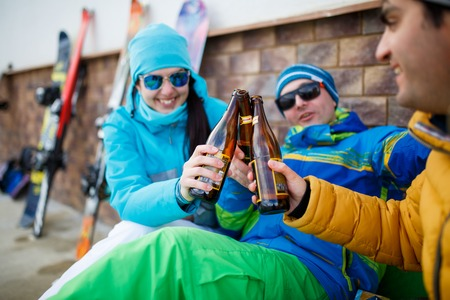 Photo of happy men and women in sunglasses with beer on winter day
