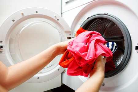 Photo of girl hands folding things in washing machine