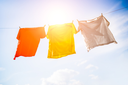 Photo of three T-shirts hanging on rope against blue sky background