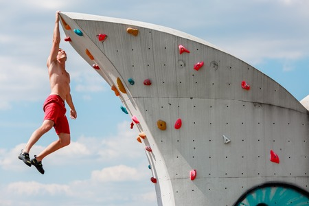 Photo of trained sports man in red shorts hanging on wall for rock climbing against blue sky with clouds