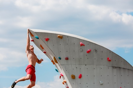 Photo of trained sports guy in red shorts hanging on wall for rock climbing against blue sky with clouds Stock Photo
