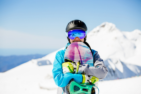 Photo of woman tourist in helmet looking into camera with snowboard in hands Standard-Bild