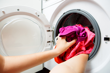 Photo of woman hands folding pink things in washing machine with open door Stock Photo