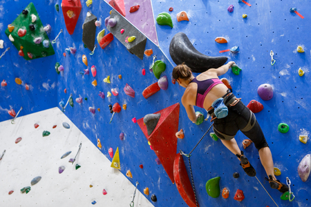 Photo of sports girl from back with bag for talc climbing on wall Stock Photo