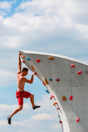 Photo of trained sports brunet in red shorts hanging on wall for rock climbing against blue sky with clouds