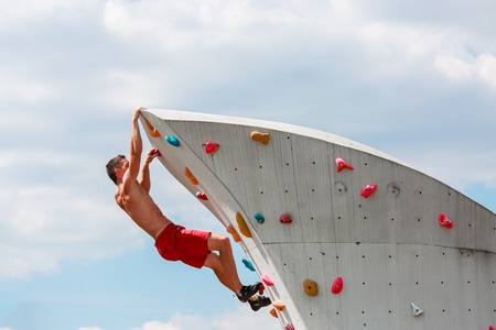 Photo of young sporty man in red shorts practicing on wall for rock climbing against blue sky with clouds Stock Photo