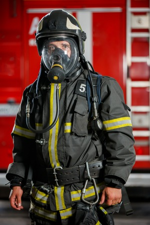 Photo of fireman in gas mask and helmet near fire engine