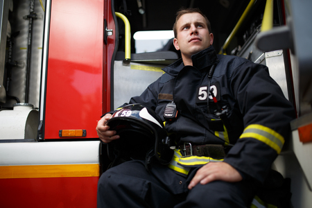 Photo of young fireman with helmet in hands sitting in fire engine
