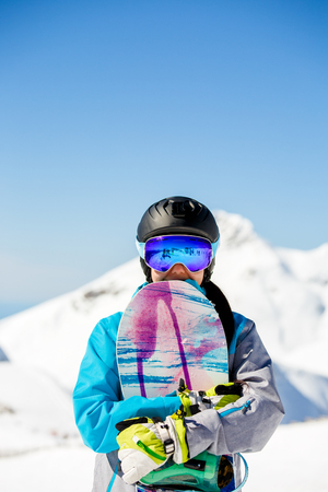 Photo of young tourist girl in helmet looking into camera with snowboard in hands on background of snow mountains