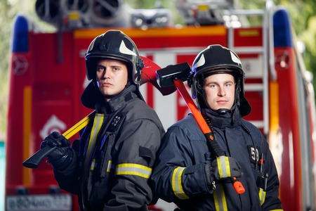 Photo of two firemen men in camera with axes in hands near fire engine Фото со стока