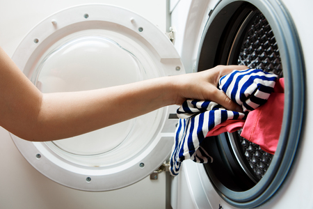 Photo of female hands folding things in washing machine with open door