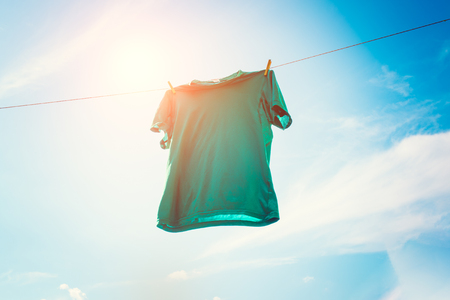 Photo of green T-shirt hanging on rope against blue sky background.