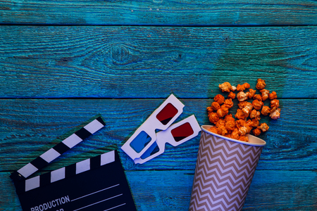 Clapperboard, glasses and popcorn on blue wooden background top view with copyspace