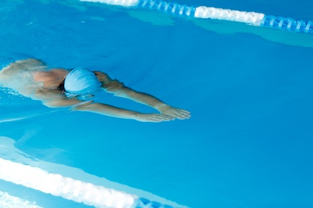 Photo of athlete man in blue cap floating on path in pool during workout