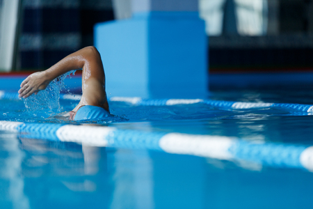 Photo of sports man in swimming cap swimming in pool during training