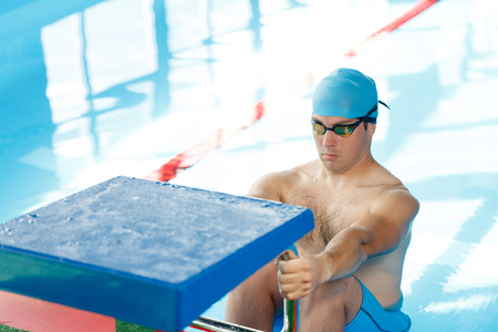 Athlete swimmer in blue cap at side in pool