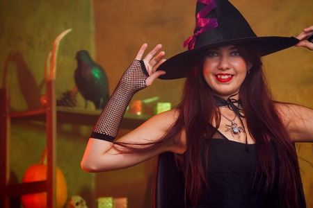 Image of witch in black dress and hat in magic room Stock fotó