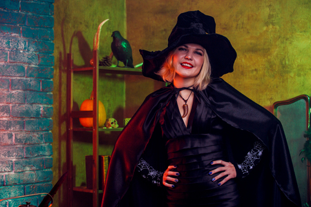 Smiling witch in black hat, dress on background of rack with pumpkin and crow