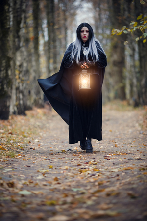 Witch girl with burning lantern in hands Stok Fotoğraf