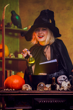 Young witch in black hat with book of spells at table with pot, pumpkin,