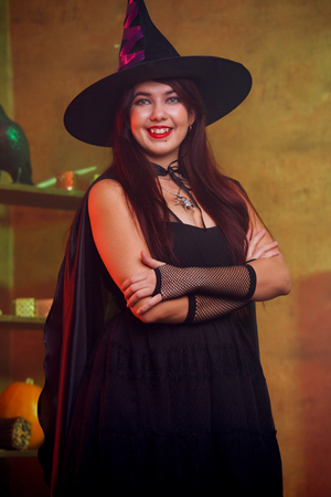 Witch in black dress and hat in magic room