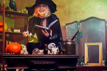 Smiling witch in black hat reading spell over pot with green steam