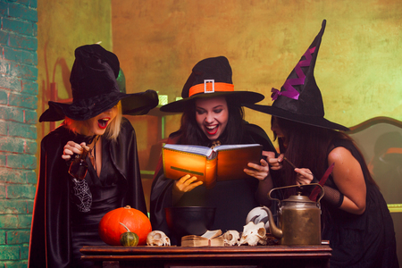 Picture of three witches with book of predictions in hands Stock fotó