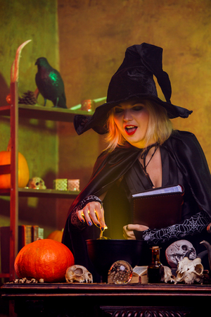 Portrait of witch in black hat with spell book at table with pot, pumpkin