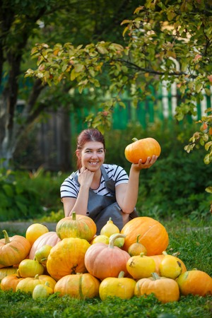 Image of woman gardener with pumpkin in hand among crop of pumpkins on green lawn Stock Photo