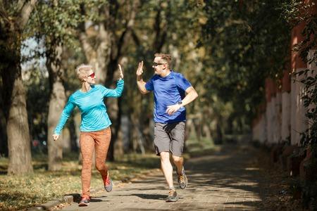 Sporting man and woman doing handshake on morning jog