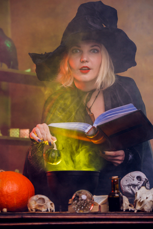 Image of young witch in black hat with book brewing potion in pot