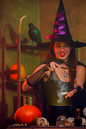 Witch in black hat with magic wand and cauldron