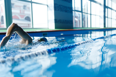 Image of sports man swimming in pool indoors