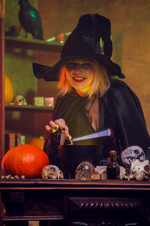 Portrait of young witch in black hat with book brewing potion in pot Archivio Fotografico