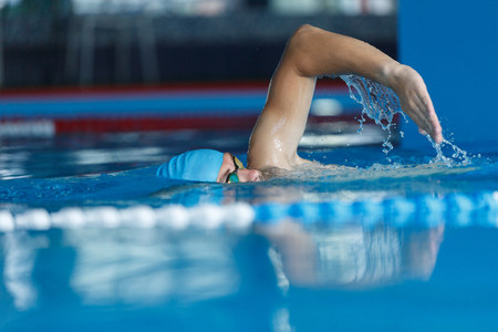 Young athlete in blue cap swimming in pool