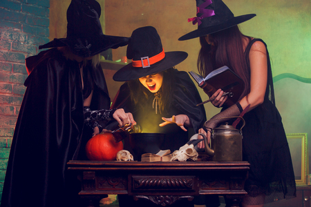 Portrait of three witches with book of boiling potions at cauldron 免版税图像
