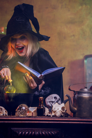 Witch reading spell pumpkin in hand