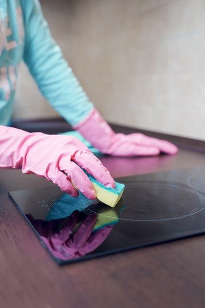 Image of female hands in pink rubber gloves washing hob
