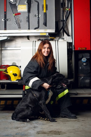 Picture of female firefighter with black dog sitting on background of fire truck