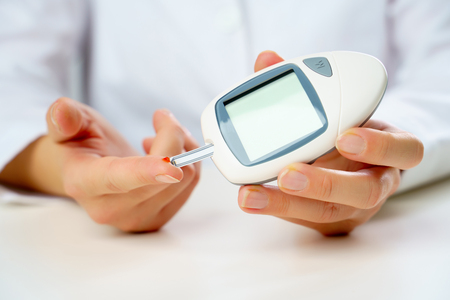 Image of patients hand with glucometer.