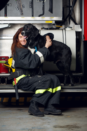 Portrait of young woman firefighter with black dog sitting on background of fire truck Stock Photo