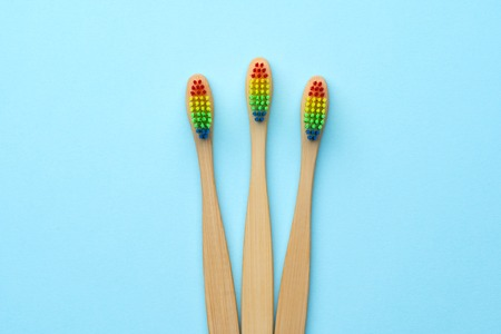 Image of three wooden toothbrushes with rainbow-colored bristles. Stock Photo